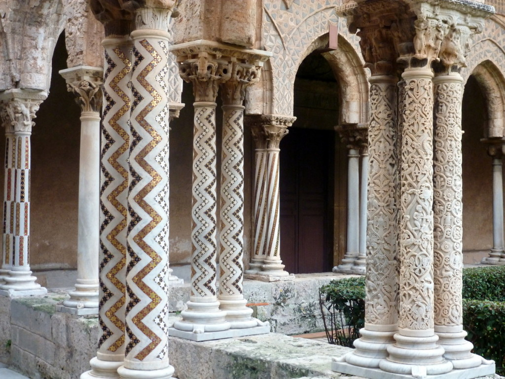 A assortment of columns in the corner with a fountain.